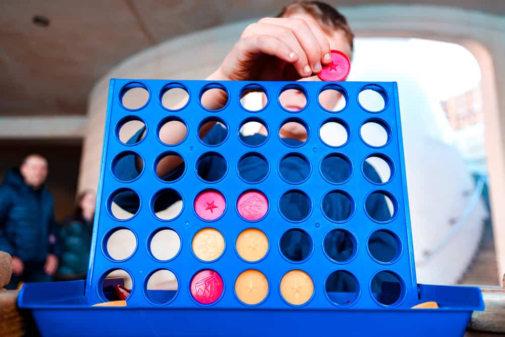 Child playing a traditional strategy game of connect 4