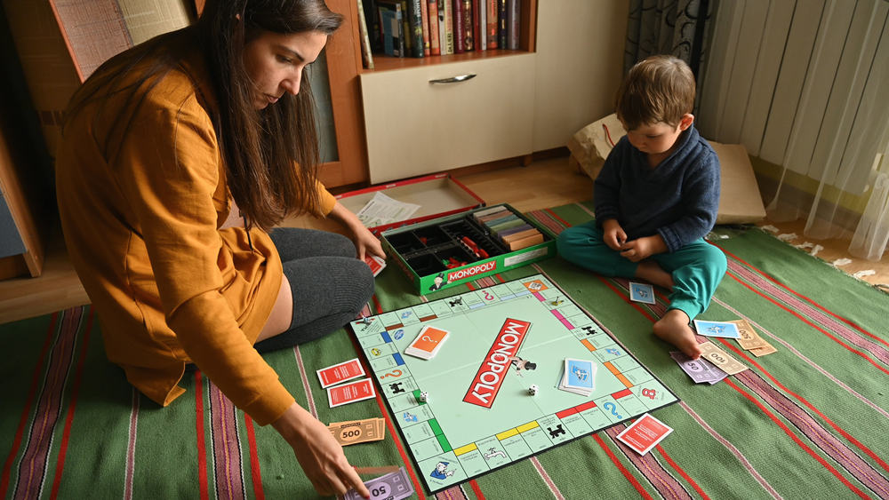 Child with mother playing the board game, monopoly