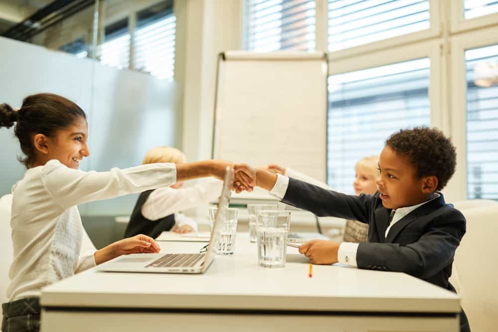 Children as business people greet each other with a handshake during the negotiations