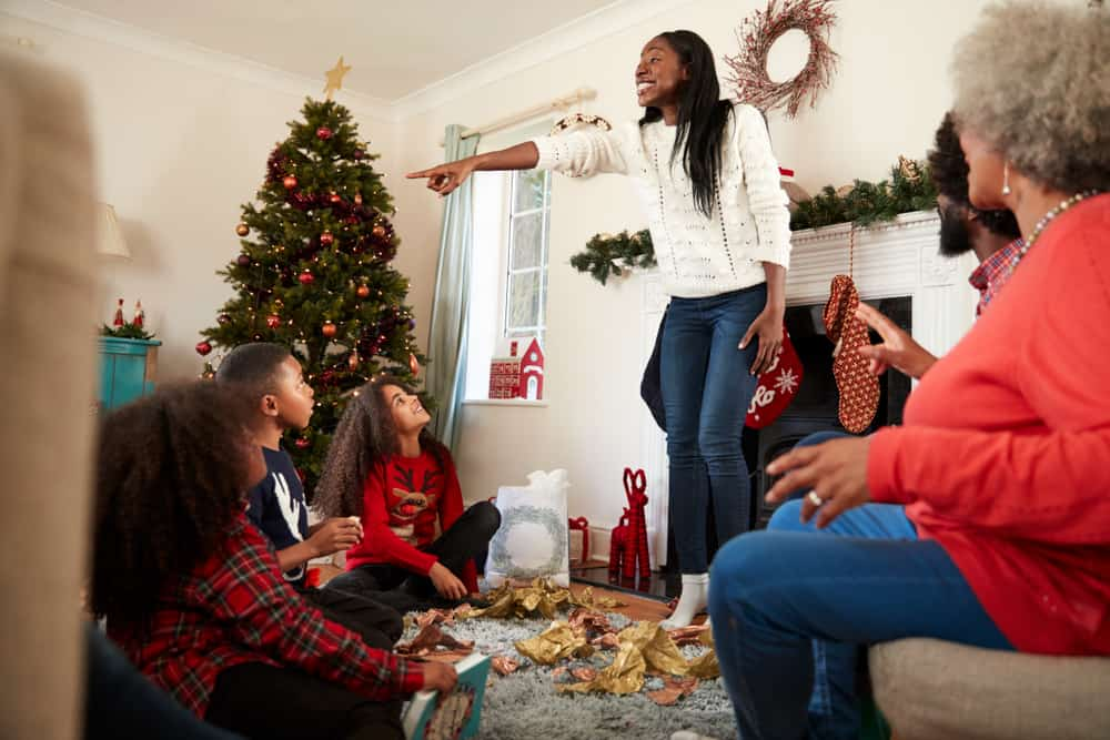 Family Playing Game Of Charades As They Celebrate Christmas At Home 2