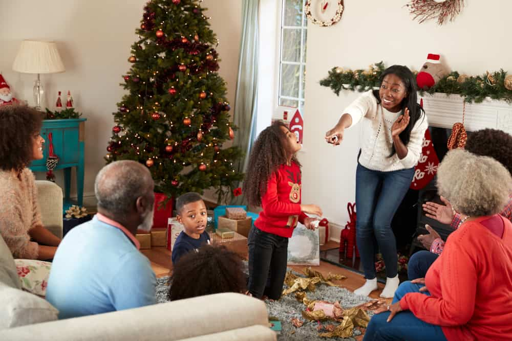 Family Playing Game Of Charades As They Celebrate Christmas At Home Together