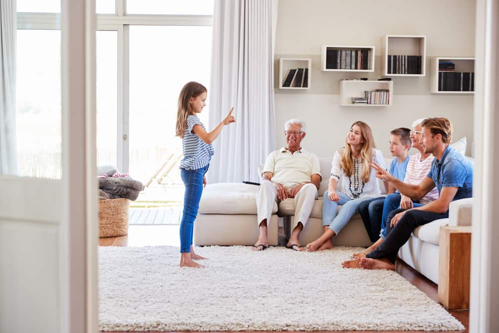 Family Sitting On Sofa At Home Playing Charades, girl acting