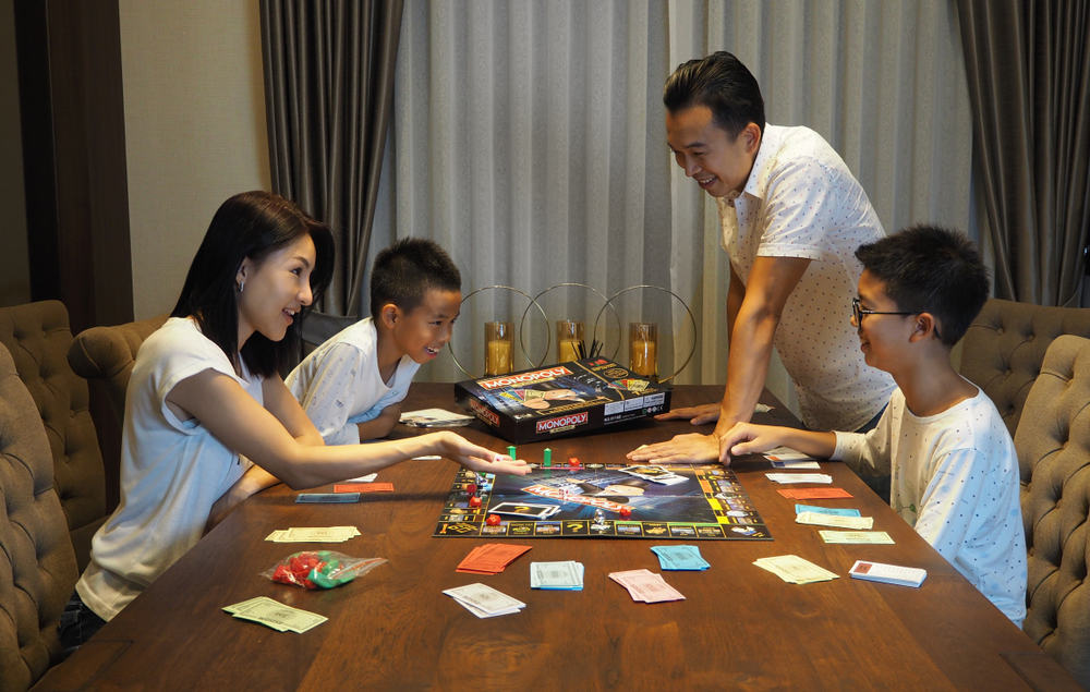 Family playing Monopoly board game together