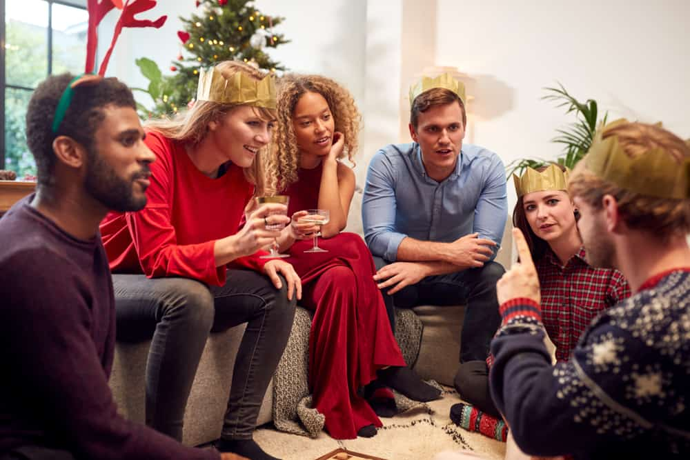 Group Of Friends Playing Charades After Enjoying Christmas Dinner
