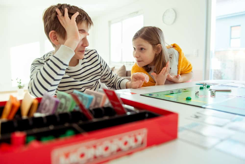 Happy children having fun playing the board game, monopoly