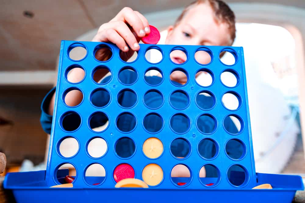 Kid playing a traditional strategy game, connect 4