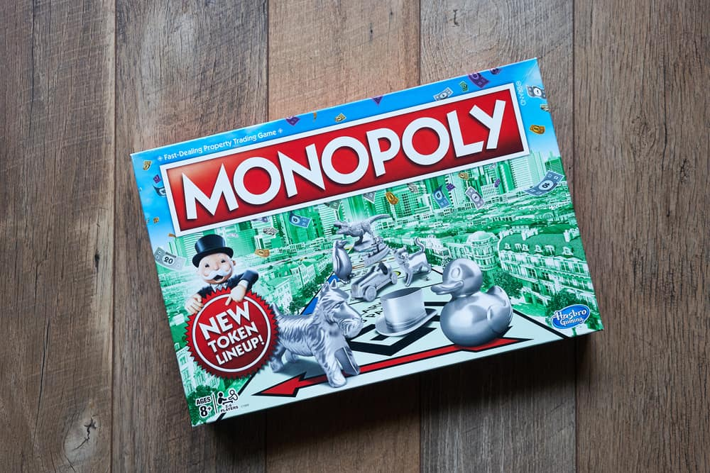 Monopoly board game box isolated on a wooden flooring background