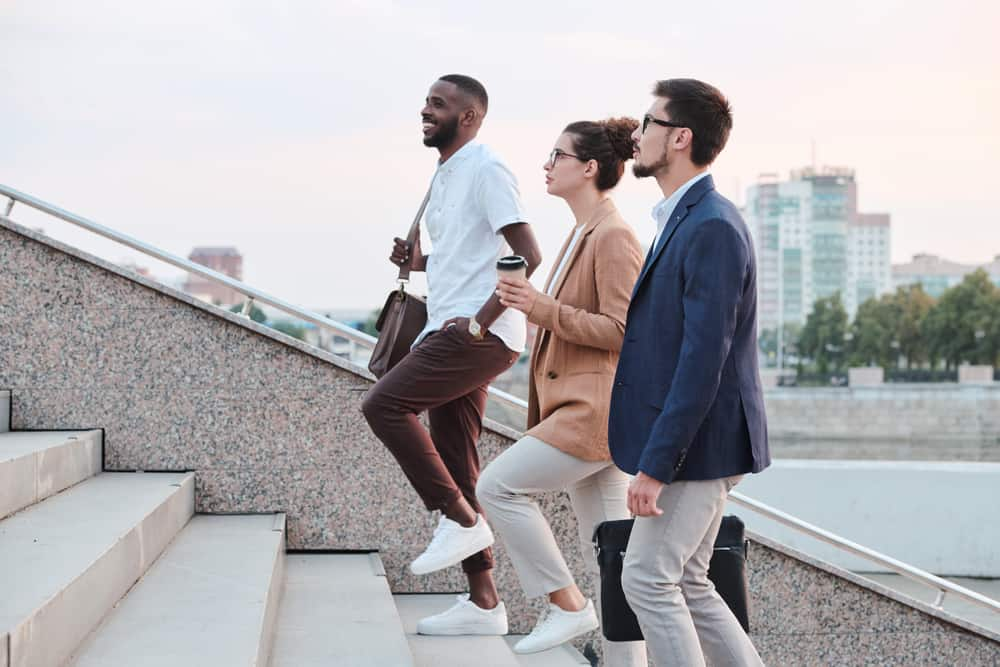 Side view of confident multi-ethnic students chatting and moving up stairs