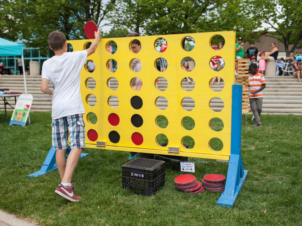 Two boys playing a giant-sized version of Connect Four outdoors