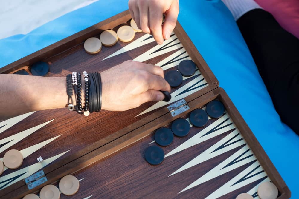 Two friends playing backgammon at home