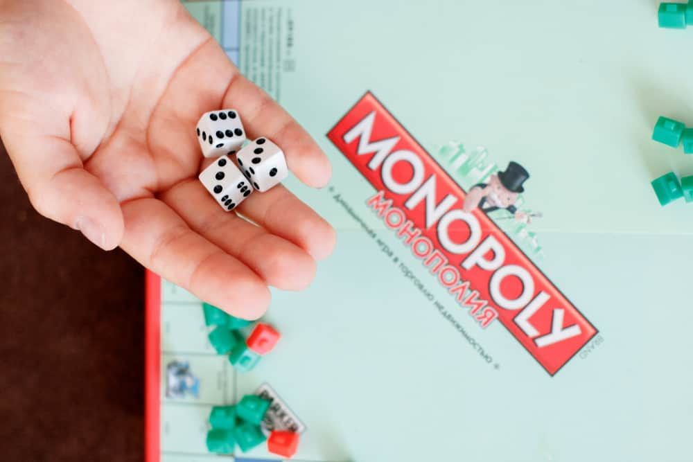 a child throws dice into the game Monopoly