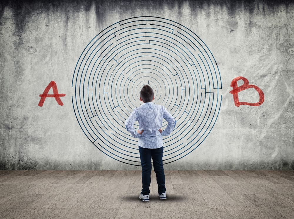 boy looking at a maze on wall. Problem solving concept