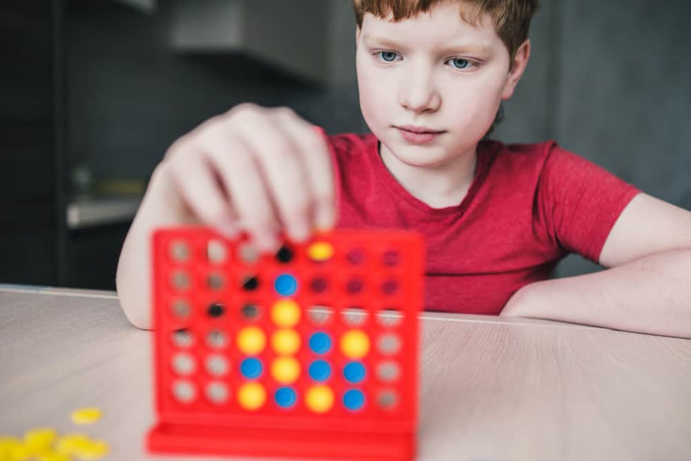 boy playing four in a row