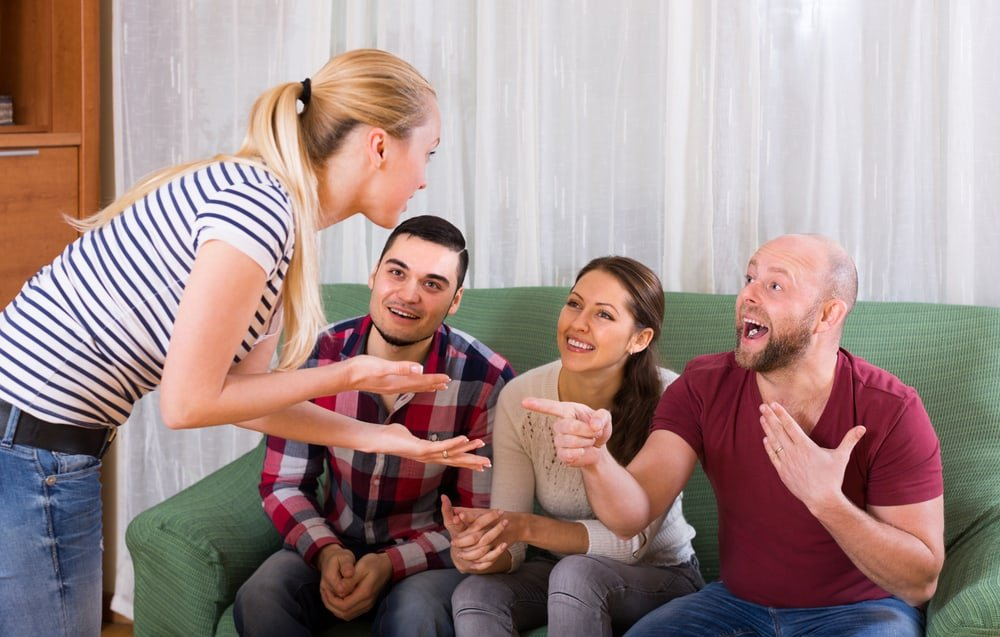 couples playing charades indoor and laughing