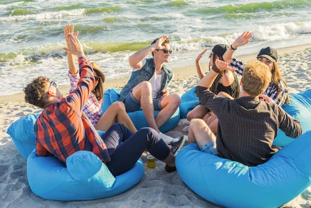 group of friends on the beach sitting on bean bags