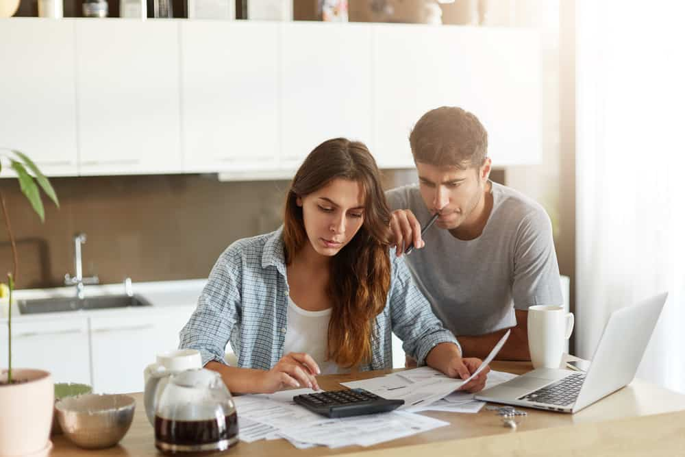 woman calculating something on calculator, holding documents in hands while her husband leaning at her shoulder
