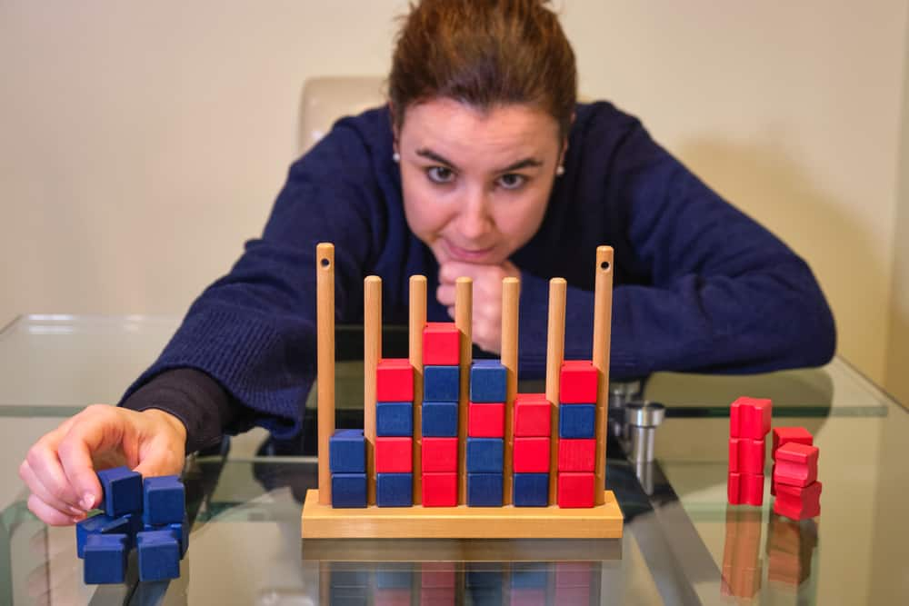 woman playing the board game connect four with red and blue pieces