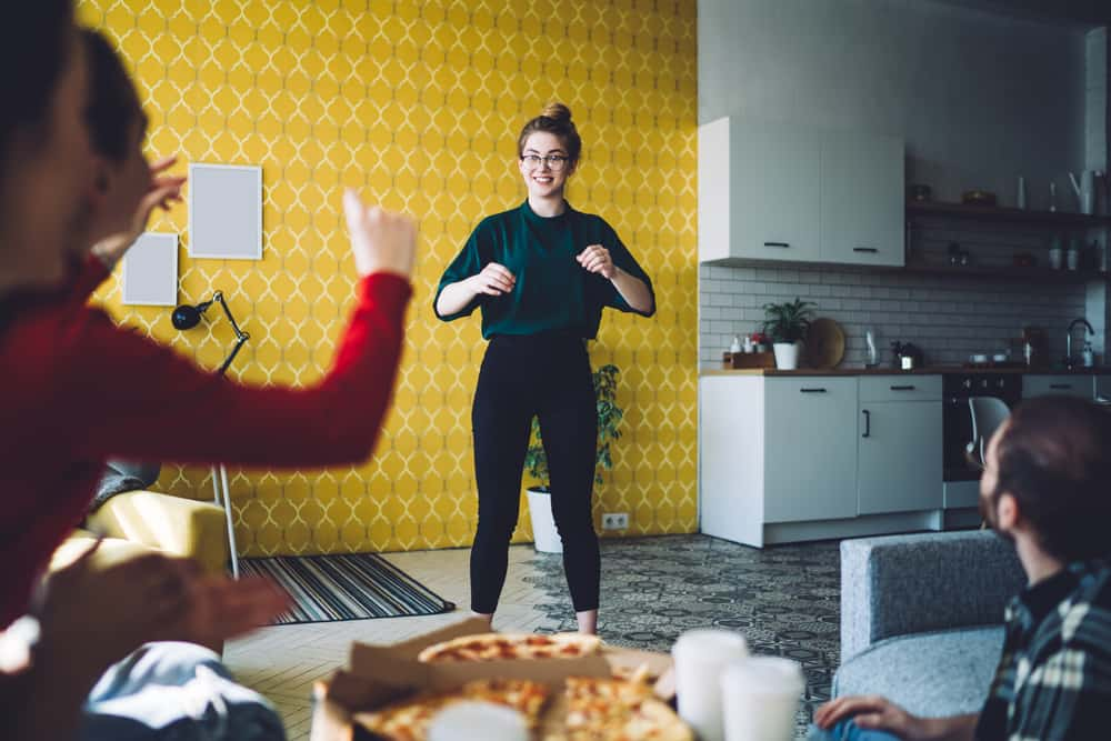 woman smiling and gesturing for interested friends while playing charades