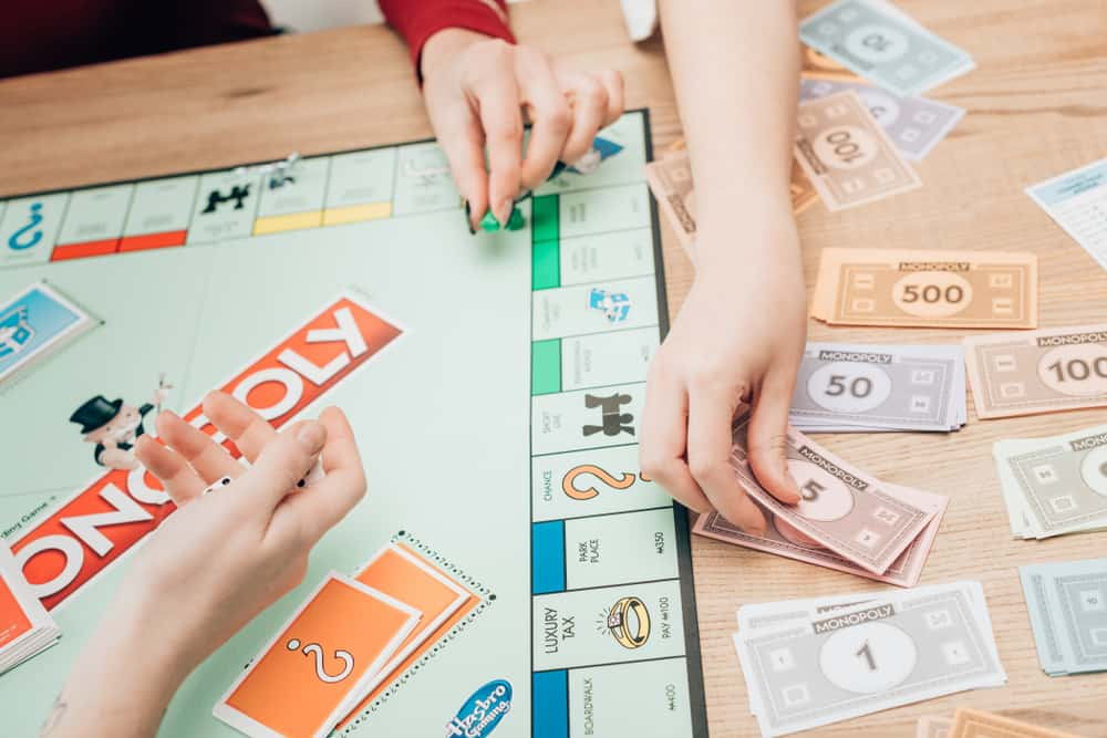 women playing monopoly game at table