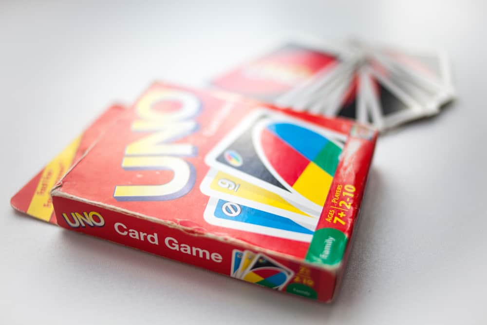 box of Uno card game and cards on white background closeup