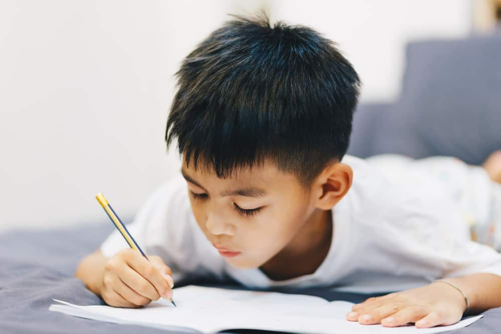 kid on bed working on a word search puzzle