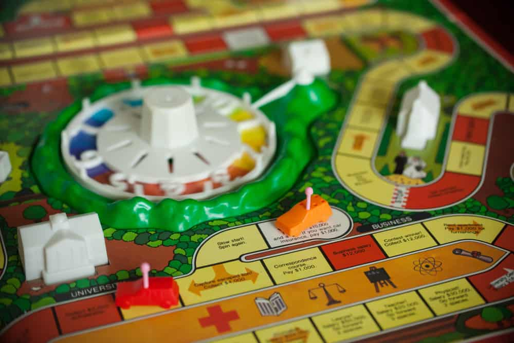Board game, The Game of Life, is shown with colorful pawns and background