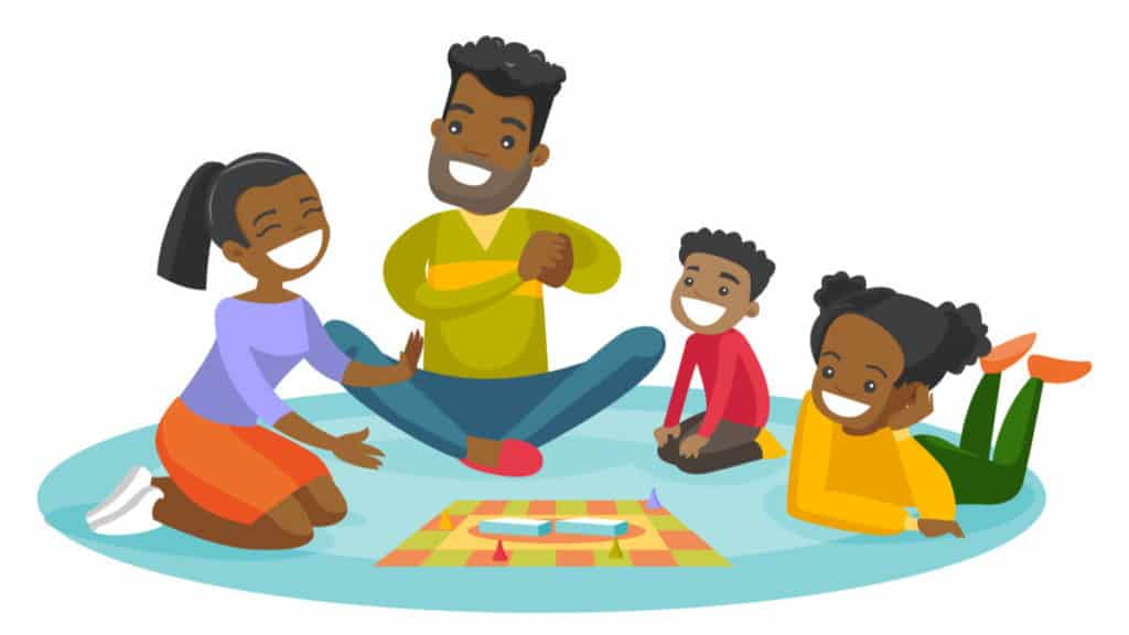 Family sitting on the floor and playing together a board game at home 2