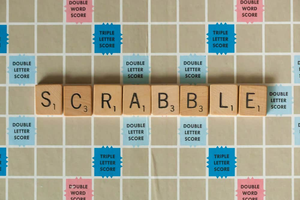 A vintage Scrabble board game is shown with letter tiles spelling out Scrabble