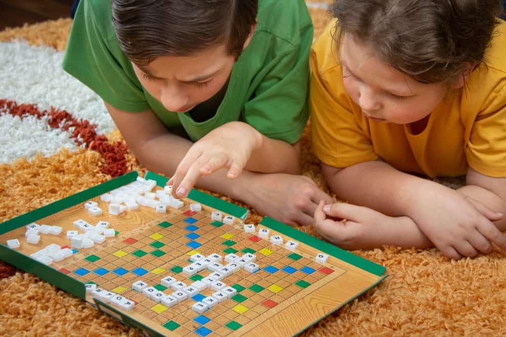 Children play in Scrabble on the floor