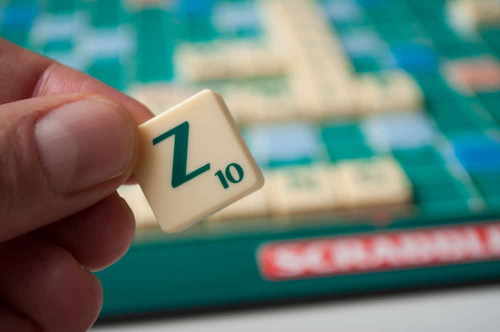Closeup of plastic letter Z in hand on Scrabble board game