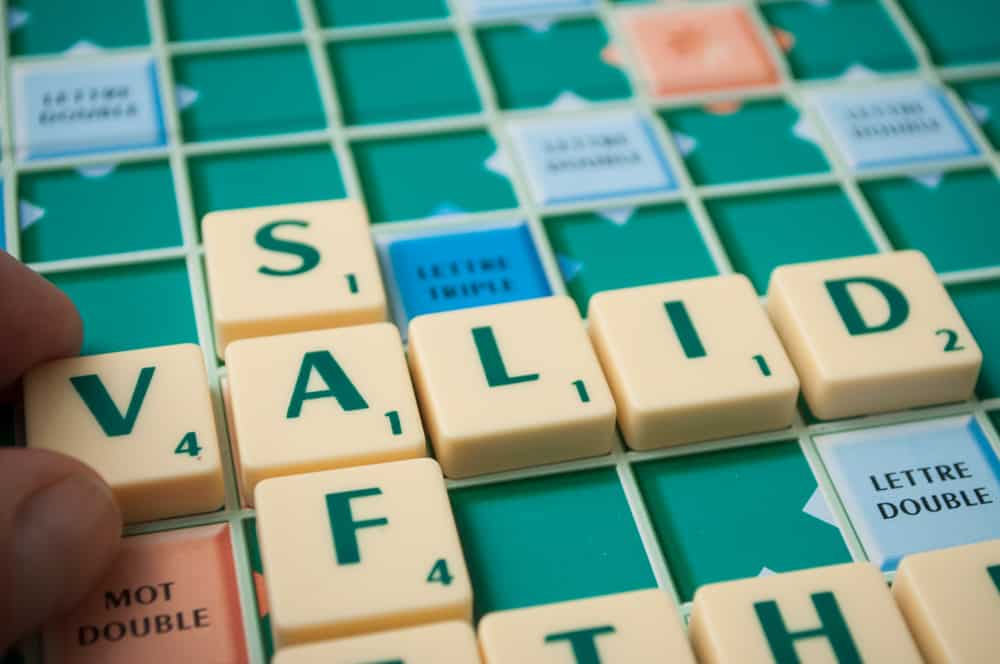 Closeup of plastic letters on Scrabble board game forming the word, Valid