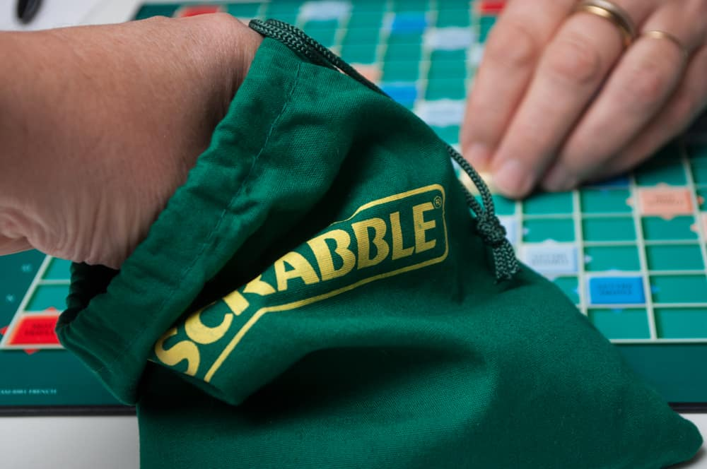 Closeup of player drawing a letter from green Scrabble bag