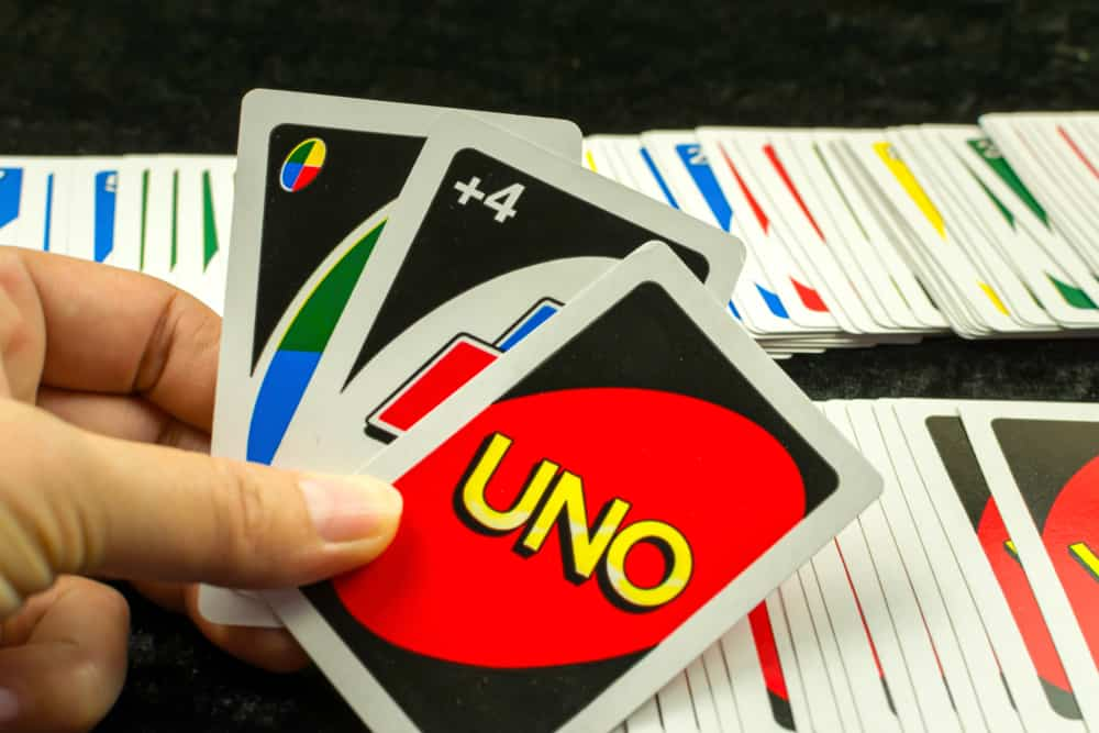 Focus of Uno cards. Woman holding the cards with black background