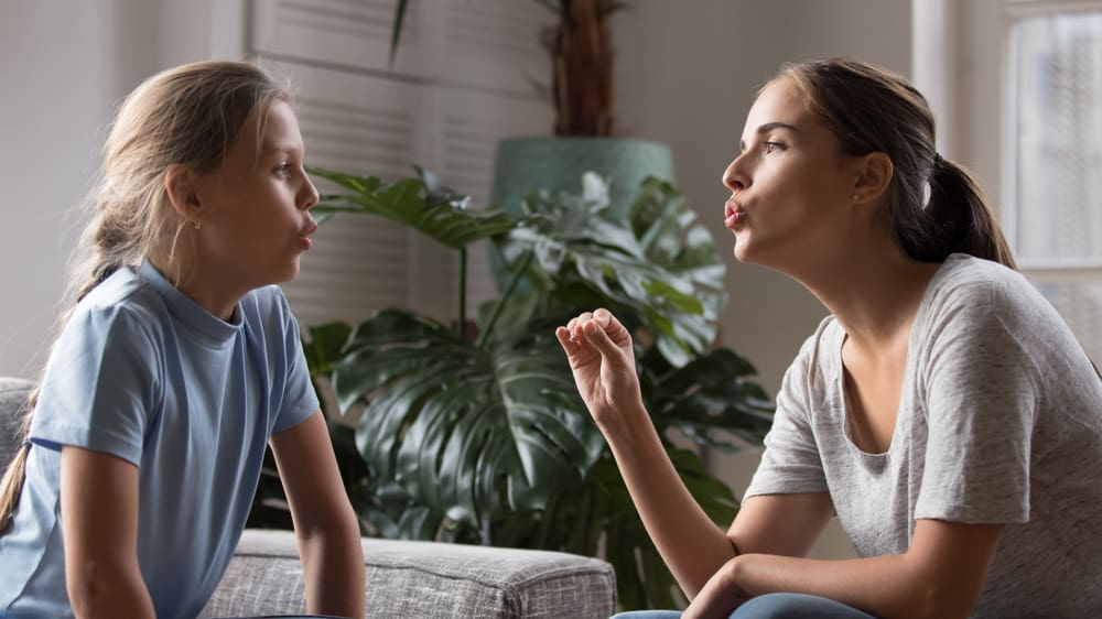 Mother and daughter working on specific word pronunciation