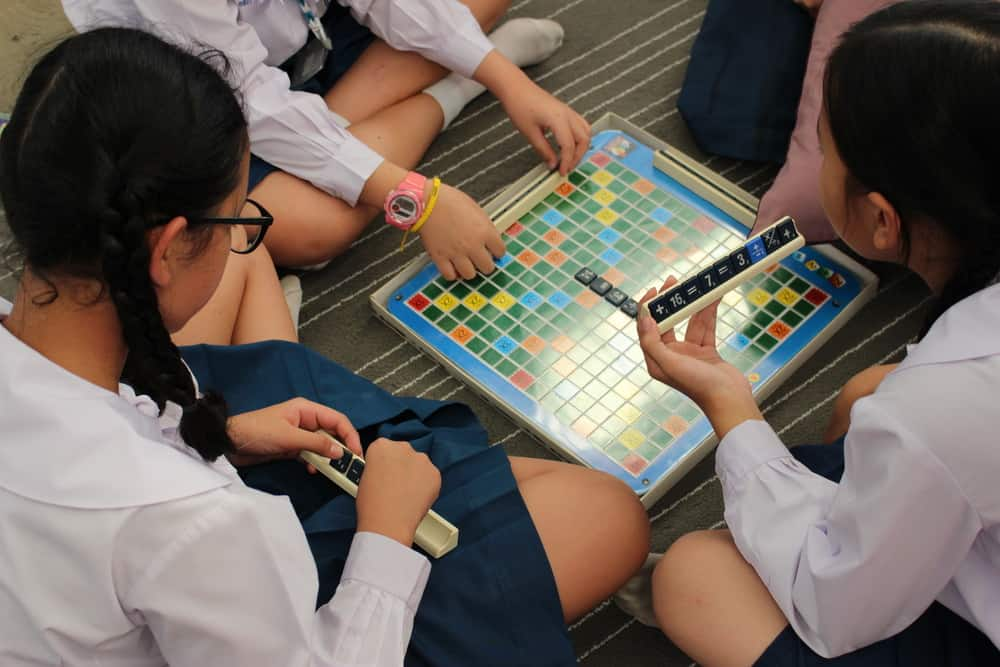 School Girls Play a Math Scrabble Style Board Game on the Floor