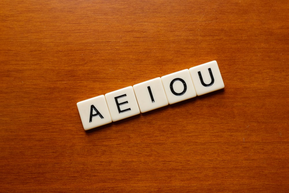 Scrabble - AEIOU vowel letters on a wood table