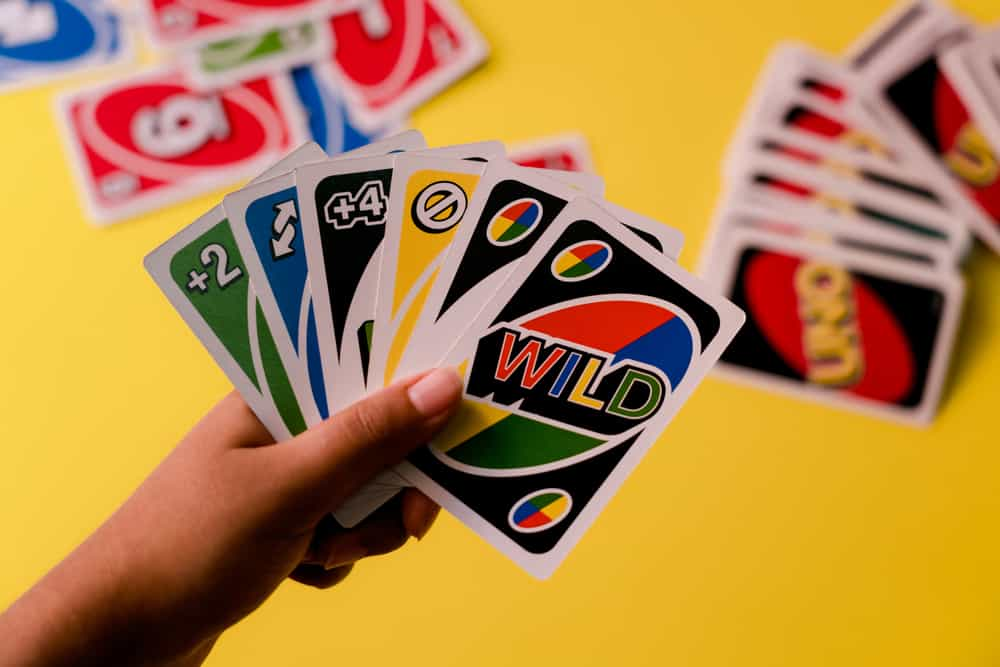 Uno special cards held against a deck of cards on a yellow background